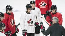 Team Canada captain Dylan Strome (19) and teammates Jake Bean (2), Mitchell Stephens (27) and Kale Clague (10) listen to head coach Dominique Ducharme during practice ahead of their quarter-final round match against the Czech Republic. (Graham Hughes/THE CANADIAN PRESS)