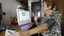 A heart patient monitors her blood pressure at home. (Albert Gea/Reuters)