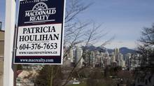 A for sale sign outside condos over looking the skyline in the Fairview neighbourhood of Vancouver, British Columbia, Monday, March 4, 2013. (Rafal Gerszak For The Globe and Mail)