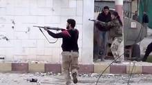 Free Syrian Army fighters fire at Syrian army soldiers during a fierce firefight in Daraa, Syria, on Thursday. The rebels captured a military base in the south. (AP)