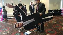 An employee of the U.S. Embassy carries a cutout of Mitt Romney,in Seoul on Nov. 7. (Ahn Young-joon/AP)