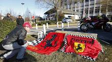 Dario, a Ferrari local fan, displays flags in front of the entrance of the emergency services at the hospital in Grenoble, French Alps, where retired seven-times Formula One world champion Michael Schumacher is (CHARLES PLATIAU/REUTERS)