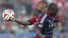 Toronto FC's Collen Warner (left) battles for the ball with Chicago Fire's Sanna Nyassi (CHRIS YOUNG/THE CANADIAN PRESS)
