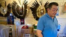 Sam George stands in front of some of his traditional head dresses in his garage on the Kettle Point reserve near Forest, Ontario May 14, 2007. (GEOFF ROBINS)