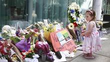 Rebecca Brown, 3, places flowers on a memorial to deceased actor Cory Monteith outside the Fairmont Pacific Rim Hotel in Vancouver on July 16, 2013. (JEFF VINNICK/THE GLOBE AND MAIL)