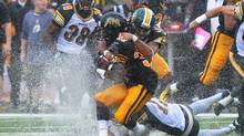 Hamilton Tiger-Cats' Lindsey Lamar, front, is tackled by Edmonton Eskimos' Calvin McCarthy, top, and Grant Shaw during first half CFL action in Guelph, Ont., Sunday, July 7, 2013. (Aaron Lynett/THE CANADIAN PRESS)