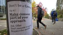 University of British Columbia students walk past a sexual assault poster on the campus in Vancouver, on October 30, 2013. (Darryl Dyck/The Canadian Press)