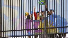 Supporters of Brazil's national soccer team wave through holes in the curtains on the fences surrounding the stadium during the team's final practice session at the Arena de Sao Paulo in Sao Paulo one day before the opening match of the soccer World Cup between Brazil and Croatia June 11, 2014. (KAI PFAFFENBACH/REUTERS)