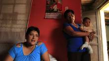 Giovanna Figueroa de Alba (L), whose husband, Javier Alba, was injured in in the crash, is next to her mother Maria Esther Yaya who is carrying Giovanna's 6-months-old baby Ashraf Alba at their home in Comas. (Pilar Olivares for The Globe and Mail/Pilar Olivares for The Globe and Mail)