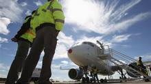Bombardier employees look at the C Series aircraft, after its first test flight in Mirabel, Quebec, September 16, 2013. (CHRISTINNE MUSCHI/REUTERS)