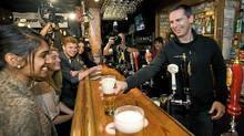 Ontario Premier Dalton McGuinty serves beer after speaking about his party's plan to make post-secondary education more accessible and affordable while at the Regal Beagle pub. (Aaron Vincent Elkaim/The Canadian Press/Aaron Vincent Elkaim/The Canadian Press)