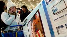 An unidentified woman talks on her cellphone about the new 40-inch Samsung LCD-TV in her cart on Black Friday at the Fair Lakes Best Buy store on November 25, 2011 in Fairfax, Virginia. Prices were deeply discounted on lots of electronic items. People camped out for days to be first in line and the line of customers went down the street. ///// malls in California and Virginia were suspending a pilot project that tracked shoppers' movements, using cellphone signals to learn more about their behaviour. (PAUL J. RICHARDS/AFP/Getty Images/PAUL J. RICHARDS/AFP/Getty Images)