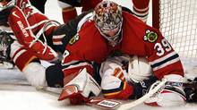 Chicago Blackhawks goalie Nikolai Khabibulin, top, of Russia, tumbles over Calgary Flames' Tony Amonte during the first period of an NHL hockey game Sunday, March 25, 2007, in Chicago.(AP Photo/Nam Y. Huh) (Nam Y. Huh)