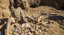 A very young girl breaks up rock at an abandoned state-owned copper mine in the city of Kipushi in the Democratic Republic of Congo, May 10, 2012. (John Lehmann/The Globe and Mail)