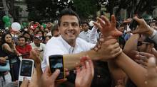 Enrique Pena Nieto, presidential candidate of the opposition Institutional Revolutionary Party (PRI), shakes hands during a political rally in Oaxaca April 10, 2012. (REUTERS)