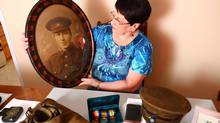 This handout photo of Diana Snow was taken in St. John's, N.L., on Sun. Aug. 10, 2014, with a portrait of her grandfather, William Newell, one of the First 500 volunteers who signed up to fight in the First World War when Newfoundland was still a British dominion. On the table in front of her is what remains of her grandfather's original military kit. (Mike Wert/THE CANADIAN PRESS)