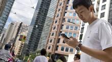 A man checks his cellphone on Bay Street in Toronto. (Gloria Nieto/The Globe and Mail)