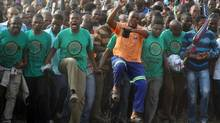 Mine workers sing a dance during a memorial service at the Lonmin Platinum Mine near Rustenburg, South Africa, on Aug. 23. Police shot and killed 34 striking miners and wounded 78 others last week. Demands for higher wages spread to at least two other mines, raising fears of further protests at more South African mines that provide most of the world's platinum. (Themba Hadebe/Associated Press)