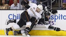 Anaheim Ducks defenseman Mark Fistric, left, checks Los Angeles Kings left wing Tanner Pearson, right, into the boards during the second period of an NHL hockey game in Los Angeles, Saturday, March 15, 2014. (Danny Moloshok/AP)
