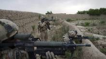 """Canadian soldiers take aim at a suspected Taliban """"trigger man"""" who may set off a remote controlled bomb in the village of Kairo Kala in Panjwaii District west of Kandahar City in April, 2010. (Louie Palu/The Canadian Press)"""