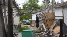 A resident surveys damage in his backyard as he returns to his home inside Fort McMurray, Alberta. (Cole Burston/AFP/Getty Images)