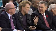 Maple Leaf Sports and Entertainment CEO Tim Leiweke (right) chats with Jon Bon Jovi as MLSE Chairman Larry Tanenbaum (left) looks on during first half NBA action between the Toronto Raptors and the Boston Celtics in Toronto on Wednesday October 30, 2013. (The Canadian Press)