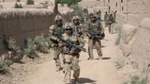 Canadian troops from 9 Platoon, C Company, PPCLI, patrol Afghan village of Zangadin for Taliban, on June 14, 2006. (John Cotter/THE CANADIAN PRESS)
