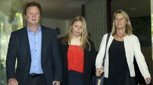 Madeleine Pulver, centre, her father Bill and mother Belinda leave the New South Wales State District Court, after the sentencing of Paul Douglas Peters, in Sydney, Australia, Nov. 20, 2012. Peters had chained a fake bomb to Madeleine in August 2011 as part of a bizarre extortion plot. (Rob Griffith/AP)