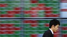 A pedestrian walks past electronic boards showing stock prices outside a brokerage in Tokyo in February, 2014. (Toru Hanai/Reuters)