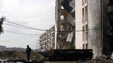 A child stands on the remnants of a destroyed military vehicle in front of a damaged building in Al Inzarat district in Aleppo February 17, 2013. (Hamid Khatib/REUTERS)