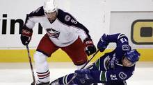 Vancouver Canucks' Henrik Sedin, (33) of Sweden, tries to maintain control of the puck after getting knocked down by Columbus Blue Jackets' Jan Hejda, of the Czech Republic, during the first period of NHL hockey action at GM Place in Vancouver, Friday, February 29, 2008. (RICHARD LAM)
