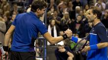Pete Sampras (right) congratulates Milos Raonic after he won 7-6, 6-1 in a celebrity tennis event in Toronto on Thursday November 17, 2011. THE CANADIAN PRESS/FRANK GUNN (FRANK GUNN/CP)
