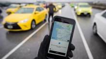 The Uber app is displayed on an iPhone as taxi drivers wait for passengers at Vancouver International Airport on Tuesday March 7, 2017. (Darryl Dyck/The Canadian Press)