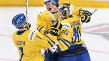 Sweden teammates Tom Nilsson, left, Linus Arnesson, centre, and Niklas Lundstrom, right, celebrate after defeating Russia in a shoot out during at the semi-final IIHF World Junior Championships hockey action in Ufa, Russia on Thursday, Jan. 3, 2013. (Nathan Denette/THE CANADIAN PRESS)