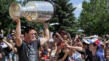 Hockey fans reach for the Stanley Cup as Chicago Blackhawks captain Jonathan Toews brings the trophy to the community centre named after him in his hometown of Winnipeg July 19, 2013. (Reuters)