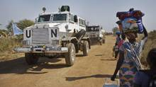 In this Dec. 30, 2013, file photo, a United Nations armoured vehicle passes displaced people walking towards the UN camp in Malakal, South Sudan. (Ben Curtis/AP)