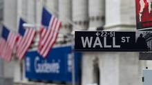 A Wall Street sign hangs near the New York Stock Exchange. (Jin Lee/Bloomberg)