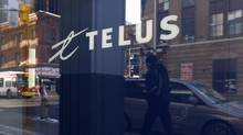 A pedestrian is reflected in the window of a Telus store while using a mobile phone in Ottawa February 11, 2011. (© Chris Wattie / Reuters/Chris Wattie /REUTERS)