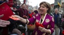 B.C. Premier Christy Clark hands out red packets during the Chinese New Year parade in Vancouver on Feb. 17, 2013. (Ben Nelms/Reuters)