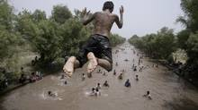 A Pakistani man jumps into a canal to cool off as temperatures reached 42 C in Lahore, Pakistan, May 26, 2013. (K.M. Chaudary/AP)