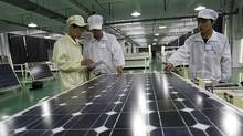 In this photo taken Wednesday March 21, 2012, Chinese workers examine solar panels at a manufacturer of photovoltaic products in Huaibei in central China's Anhui province. (AP)