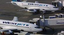 Two WestJet planes sit on the tarmac at the Calgary Airport on Aug. 24, 2001. (Jeff McIntosh)