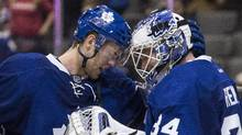 Toronto Maple Leafs new signing Peter Holland (left) congratulates goal tender James Reimer after their team defeated the Buffalo Sabres 4-2 in NHL hockey action in Toronto on Saturday November 16 , 2013. (CHRIS YOUNG/THE CANADIAN PRESS)