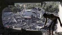 A Palestinian inspects a house which police said was damaged in an Israeli air strike that destroyed a neighbouring house in Deir El-Balah, in the central Gaza Strip, on July 14, 2014. (IBRAHEEM ABU MUSTAFA/REUTERS)