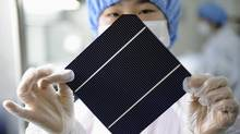 A worker displays a solar panel at a workshop in Chint Solar Co.'s factory in Hangzhou, in China's Zhejiang province. (LANG LANG/Reuters)