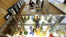 Krystal Klacsan prepares artwork to be hung on July 7, 2014, behind a case displaying glass bongs at the recreational marijuana store Cannabis City in Seattle. (TED S. WARREN/ASSOCIATED PRESS)