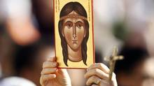 A faithful holds an image depicting Kateri Tekakwitha, the first aboriginal to be declared a saint, before Pope Benedict XVI conducts a special mass to canonize seven new saints including Kateri at St. Peter's square in Vatican City October 21, 2012. (STEFANO RELLANDINI/REUTERS)