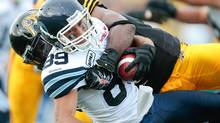 Spencer Watt of the Toronto Argonauts is tackled by Jermaine McElveen of the Hamilton Tiger-Cats in Canadian Football League action at Ivor Wynne Stadium in Hamilton, Ontario, Saturday, July 14, 2011. (Geoff Robins/THE CANADIAN PRESS)