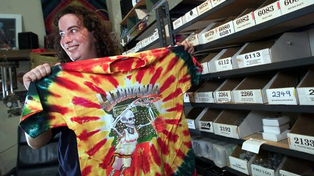 Jamie Parker, a shipper at the Grateful Dead Productions warehouse in Novato, Calif., displays a souvenir Dead tie-dyed shirt Monday Aug. 7, 2000. The shirt is among the many items from ties to sports bras to dog bowls that are stored in the warehouse where the company that survived the band's 1995 breakup runs a multimillion- dollar business. (ERIC RISBERG/AP)