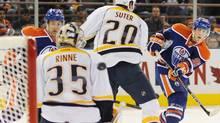 The Edmonton Oilers' Ryan Nugent-Hopkins, right, shoots past Nashville Predators goalie Pekka Rinne, during second period NHL hockey action in Edmonton, on Monday, October 17, 2011. THE CANADIAN PRESS/John Ulan (John Ulan/CP)